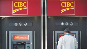 A man uses an ATM at a CIBC branch in Montreal, on April 24, 2014. (Graham Hughes / THE CANADIAN PRESS)
