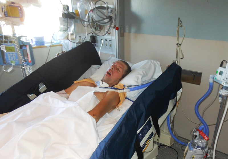 This family photo shows Alex Lozanski in a hospital bed in Vancouver, B.C. after suffering a traumatic brain injury.