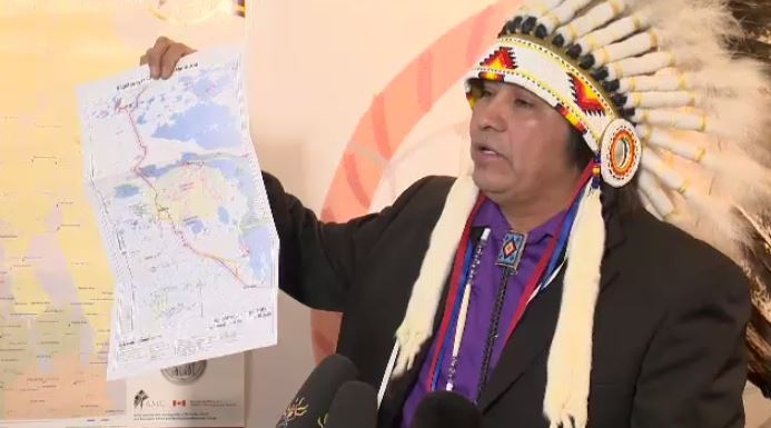 Sapotaweyak Cree Nation Chief Nelson Genaille holds a map showing the planned route for Hydro's Bipole III transmission line. (file image)