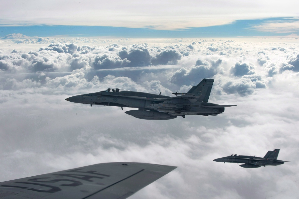 Royal Canadian Air Force CF-18 Hornets depart after refueling with a KC-135 Stratotanker assigned to the 340th Expeditionary Air Refueling Squadron on Oct. 30, 2014, over Iraq. (HO-U.S. Air Force Photo by Staff Sgt. Perry Aston / The Canadian Press)
