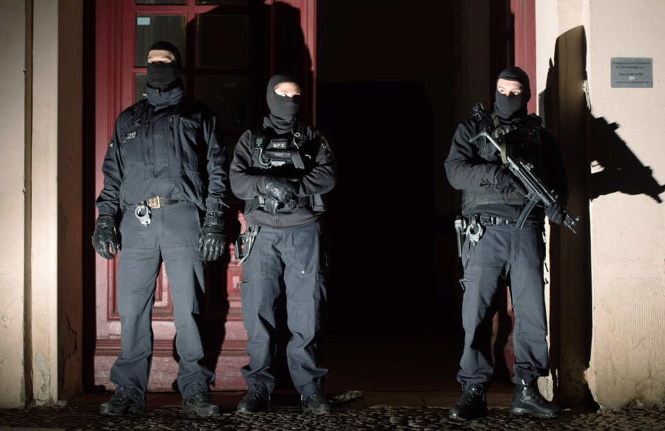 Special police force guards the entrance of a house in Berlin as police raids several residences in Berlin, Friday, Jan. 16, 2015. (AP / dpa, Lukas Schulze)