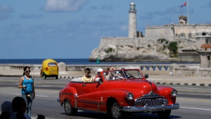 In this Oct 12, 2013 file photo, tourists ride in a classic American car on the Malecon in Havana, Cuba.  (AP Photo/Franklin Reyes, File)