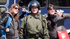 Two female demonstrators pose with a police officer in riot gear after a tentative agreement with students became public Saturday, May 5, 2012 as the Quebec Liberal Party is meeting in Victoriaville Que.. THE CANADIAN PRESS/Jacques Boissinot