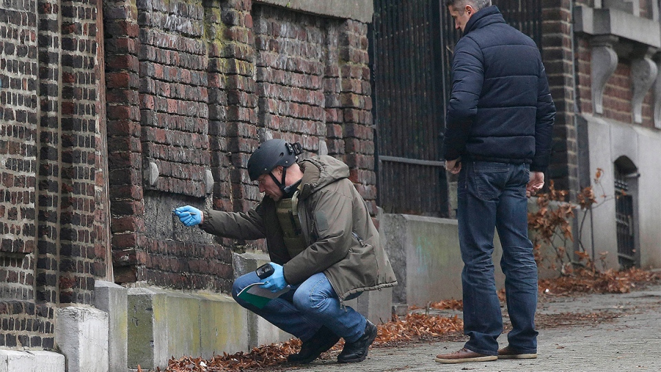 Belgian police officers examine a wall in a street in Verviers, Belgium, Friday, Jan. 16, 2015. (AP / Frank Augstein)
