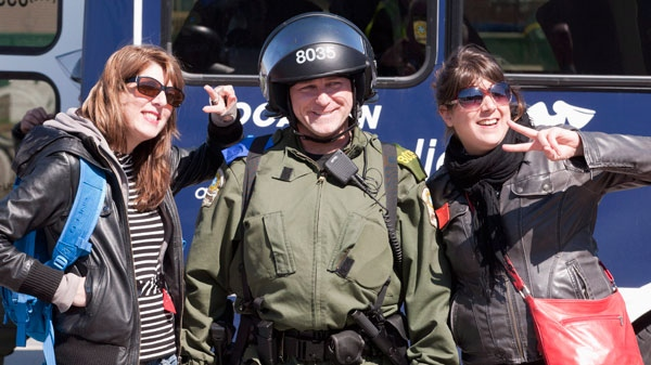 Two female demonstrators pose with a police officer in riot gear after a tentative agreement with students became public in Victoriaville Que., Saturday, May 5, 2012. (Jacques Boissinot / THE CANADIAN PRESS)