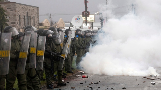 Riot police stand in a cloud of teargas in Victoriaville, Quebec. May 4, 2012. THE CANADIAN PRESS/Ja