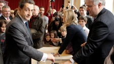 French President and UMP candidate Nicolas Sarkozy, left, casts his vote for the second round of the presidential elections in Paris Sunday May 6, 2012. (AP / Michel Euler)