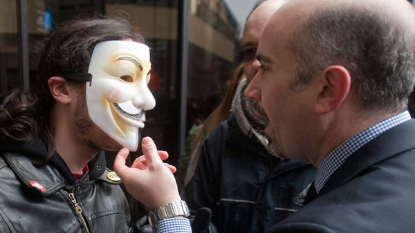 A hotel employee tries to remove the mask of a protester who was part of a crowd blocking the Delta hotel during a demonstration against higher tuition fees in Montreal, Thursday, February 16, 2012. (Ryan Remiorz / THE CANADIAN PRESS)
