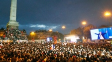 Supporters of Socialist President-elect Francois Hollande, seen on the video screen at right, celebrate after the results of the second round of the French Presidential elections were announced at Bastille square in Paris, France, Sunday, May 6, 2012. (AP / Francois Mori)
