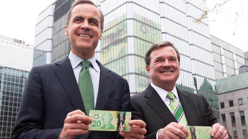 Minister of Finance Jim Flaherty and Bank of Canada Governor Mark Carney show off the new $20 bank bill during a ceremony in Ottawa