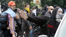 A demonstrator throws a brick through a car window in Toronto, Saturday, June 26, 2010. (AP / Gerry Broome)