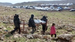 Iraqis from the Yazidi minority carry a bed frame on Mount Sinjar in northern Iraq, Monday, Jan. 12, 2015. (AP / Seivan Selim, File)
