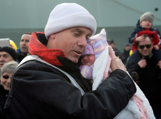 Master Seaman Kurt Sheppard holds his infant daughter Sadie for the first time as HMCS Toronto returns to port in Halifax on Sunday, Jan. 18, 2015. (Andrew Vaughan / THE CANADIAN PRESS)