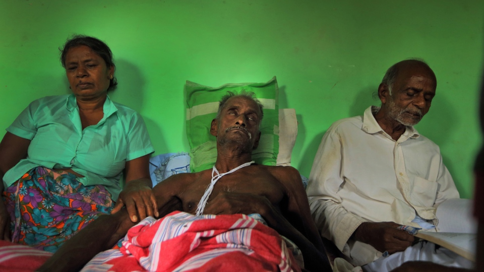 Appuhamige Pinhami, a Sri Lankan farmer suffering from a deadly mystery kidney disease, lies on a bed as family members sit by his side chanting religious scriptures expecting his death anytime, at their house in Kebithigollewa, Sri Lanka, Dec. 9, 2013, photo. (AP / Eranga Jayawardena)