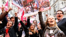 Supporters of Socialist Party candidate for the presidential election Francois Hollande celebrate with champagne after the first results of the second round of French presidential elections outside Socialist Party campaign headquarters in Paris, France, Sunday, May 6, 2012. (AP / Francois Mori)