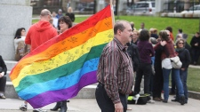 Daniel MacKay carries a rainbow flag with messages for Raymond Taavel at Grand Parade prior to a public memorial service in Halifax. N.S. on Sunday, May 6, 2012. (Ryan Taplin / THE CANADIAN PRESS)