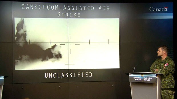 Brig-Gen. Mike Rouleau shows video of a Coalition air strike during a briefing on Canada's mission in Iraq, in Ottawa, Monday, Jan. 19, 2015.