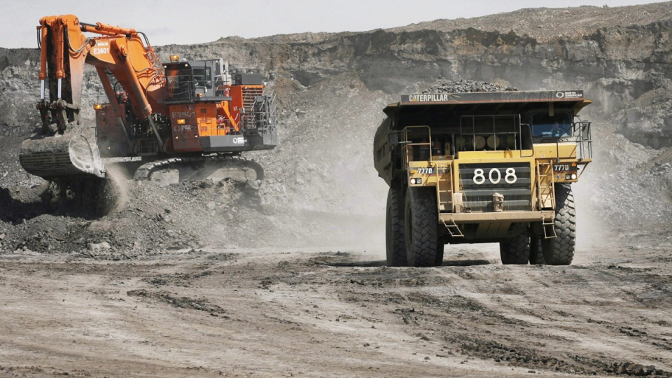 A haul truck carrying a full load drives away from a mining shovel at the Shell Albian Sands oilsands mine near Fort McMurray, Alta., Wednesday, July 9, 2008. (Jeff McIntosh / THE CANADIAN PRESS)