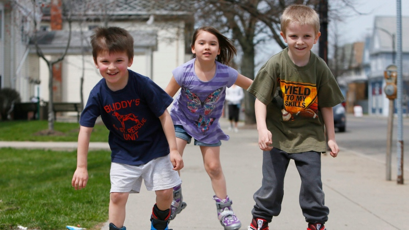 Kids getting fresh air, sunshine and exercise. From left, Allen Armstrong, 4, Hannah Armstrong, 6, and Brian Kuhn, 7, speed down the sidewalk on Tonawanda Street in Buffalo, N.Y., on inline skates, Tuesday afternoon, April 23, 2013. (AP / The Buffalo News, Derek Gee)
