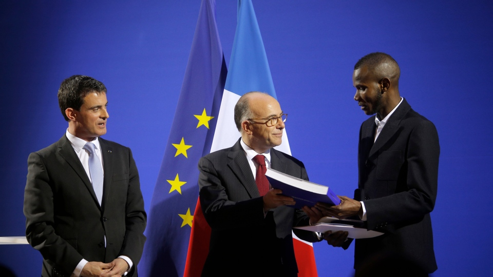 French Prime Minister Manuel Valls, left, and French Interior Minister Bernard Cazeneuve, centre, award citizenship to Lassana Bathily during a ceremony in Paris, Tuesday, Jan. 20, 2015.  (AP / Christophe Ena)