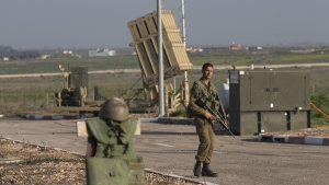 In this file photo, an Israeli soldier guards an Iron Dome air defense system deployed in the Israeli controlled Golan Heights near the border with Syria, Tuesday, Jan. 20, 2015. (AP / Ariel Schalit)