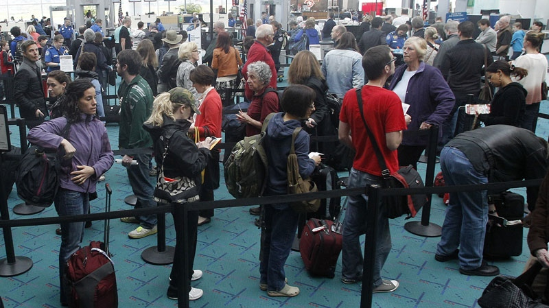 This April 30, 2012, photo shows travelers passing through the security check point at Portland International Airport, in Portland, Ore. (AP / Rick Bowmer)