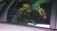 A suspect, who was arrested after police conducted several early morning raids in the Montreal area, gives the peace sign on Wednesday, May 9, 2012.