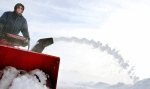 Using a snow blower Mel Fuglsang clears snow from the driveway of his rural home near Welton, Iowa on Tuesday, Jan. 6, 2015. (The Quad City Times, Kevin E. Schmidt / AP Photo)