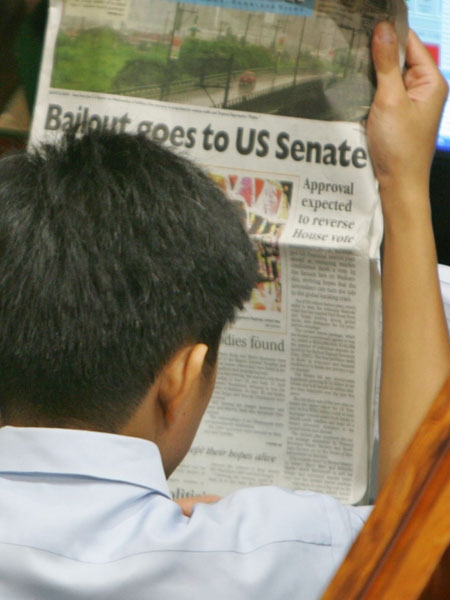 A trader reads the paper headlining the current U.S. financial proposed bailout during trading at the Philippines Stock Exchange Thursday, Oct. 2, 2008. (AP  / Pat Roque)