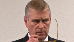 Prince Andrew, puts on his glasses prior to his speech to business leaders during a reception at the sideline of the World Economic Forum in Davos, Thursday, Jan. 22, 2015. (AP Photo/Michel Euler, Pool)
