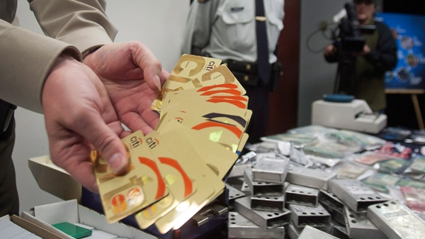 A Quebec Provincial Police officer shows some of the confiscated credit cards and technology at a news conference about the dismantleing of a $100 million worldwide credit card fraud ring in Montreal, Wednesday, May 9, 2012. (Ryan Remiorz / THE CANADIAN PRESS)