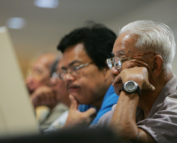 Traders closely monitor the ongoing trading at the Philippines Stock Exchange in Manila's financial district of Makati, Thursday, Oct. 2, 2008. (AP / Pat Roque)