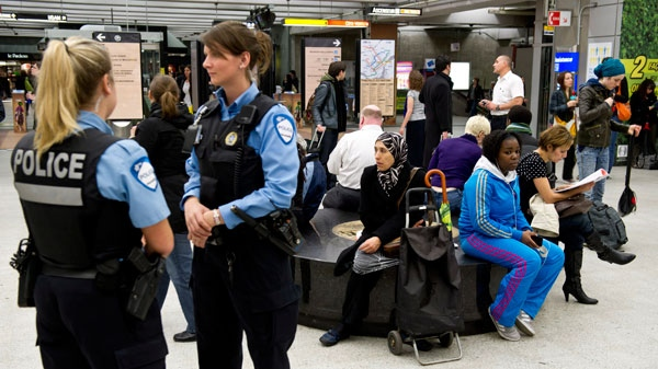 Police officers stand by as commuters wait for the reopening of the subway after smoke bombs closed the whole Montreal subway system Thursday, May 10, 2012. (Paul Chiasson / THE CANADIAN PRESS)