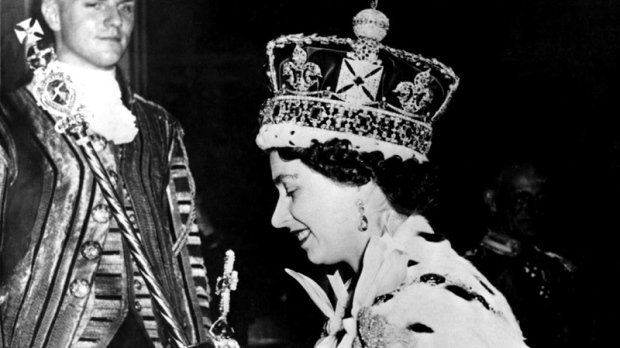 Queen Elizabeth II, wearing the Imperial Crown, carries the symbols of authority, the orb and the and sceptre, as she leaves Westminster Abbey at the end of the Coronation Ceremony, June 2, 1953. (AP Photo)
