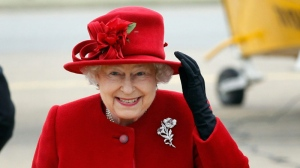 Queen Elizabeth II holds on to her hat in high winds during a visit to RAF Valley, Anglesey, Wales, where her grandson Prince William, is stationed as a search and rescue helicopter pilot Friday April 1, 2011. (AP / Christopher Furlong)