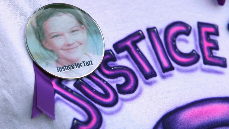 Patrina Fraser, girlfriend of Rodney Stafford, wears a t-shirt and button with the message 'Justice for Tori', outside the courthouse at the Michael Rafferty murder trial in London, Ont., Friday, May 11, 2012. (Dave Chidley / THE CANADIAN PRESS)