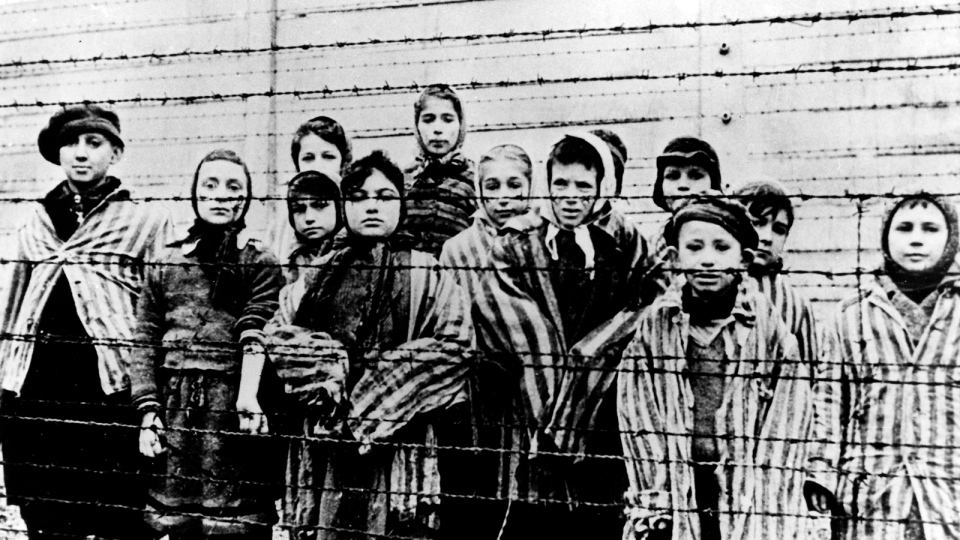 A picture taken just after the liberation by the Soviet army in January, 1945, shows a group of children wearing concentration camp uniforms behind barbed wire fencing in the Auschwitz Nazi concentration camp. (AP Photo)