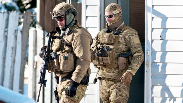 RCMP officers perform door-to-door checks on Cedar Street in Moncton, N.B. after reports of a man walking around with a weapon on Sunday, Jan. 25, 2015. (Marc Grandmaison / THE CANADIAN PRESS)