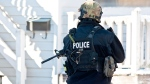 An RCMP officer performs door-to-door checks on Cedar Street in Moncton, N.B. after reports of a man walking around with a weapon on Sunday, Jan. 25, 2015. (Marc Grandmaison / THE CANADIAN PRESS)