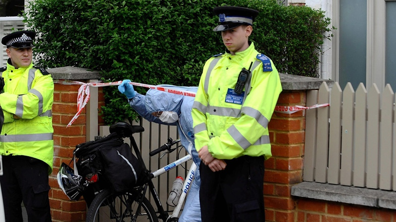 A Police forensics officer leaves a house in Wandsworth, south London, on Thursday May 10, 2012, after two babies were found dead late Wednesday night.  (AP /Clive Gee)