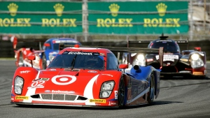 Joao Barbosa (5) of Portugal, leads Jordan Taylor, left, through the East horseshoe turn during the final hours of the IMSA 24 hour auto race at Daytona International Speedway in Daytona Beach, Fla., Sunday, Jan. 25, 2015. (AP / David Graham)