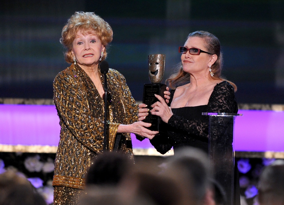 Carrie Fisher, right, presents Debbie Reynolds with the Screen Actors Guild life achievement award at the 21st annual Screen Actors Guild Awards at the Shrine Auditorium on Sunday, Jan. 25, 2015, in Los Angeles. (Photo by Vince Bucci/Invision/AP)