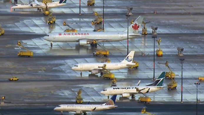 Planes wait to be de-iced in Toronto on Monday, Jan. 26, 2015.