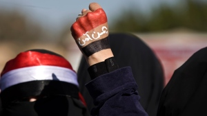 "A woman raises her fist painted with Yemen's flag and Arabic writing that reads, ""Yemen is safe,"" to protest against Houthi Shiite rebels on Jan. 24, 2015. (AP / Hani Mohammed)"