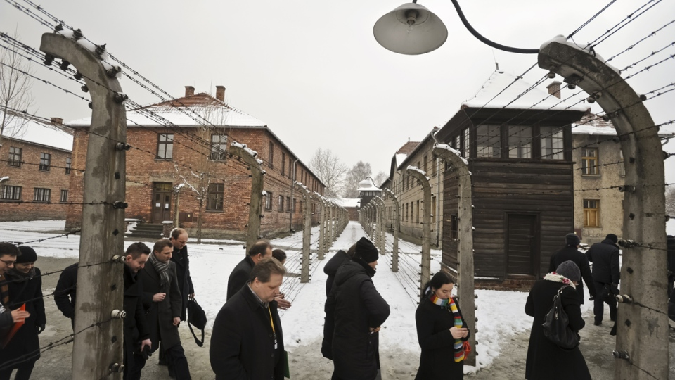 Visitors walk by barbed wire fences at the Auschwitz Nazi death camp in Oswiecim, Poland, Monday, Jan. 26, 2015. (AP / Alik Keplicz)