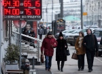 People walk past a money exchange office with a sign showing currency exchange rates in Moscow, Tuesday, Jan. 20, 2015. (AP / Pavel Golovkin)