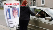 Tiffany Ackers hands out a poster for then missing Victoria Stafford, 8, on a street corner in Woodstock, Ont. on Friday April 10, 2009. (Dave Chidley / THE CANADIAN PRESS)