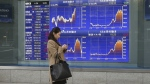 A woman walks by an electronic stock board of a securities firm in Tokyo Monday, Jan. 26, 2015. (AP / Koji Sasahara)