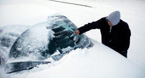 Jose Cardenas scrapes the snow and ice from his windshield in this file photo. (AP Photo/Statesman-Journal, Kobbi R. Blair)