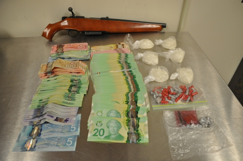 A shotgun, drugs and cash seized from a home on Pond Mills Road are seen in this photo released by the London Police Service on Tuesday, Jan. 27, 2015.
